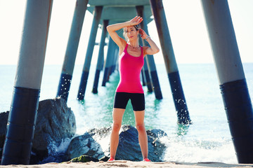 Female runner with muscular slim body resting on the beach