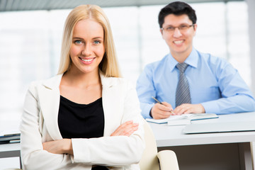 Successful business woman sitting with her collegue at office