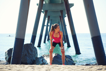 Attractive woman resting after intensive run on the beach,