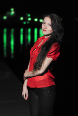 Beautiful girl in red blouse with night lights