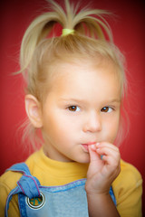 Little girl with finger on mouth
