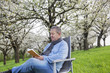 Man reading in the book under blooming cherry tree