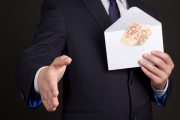 bribery concept - man in suit with money in envelope ready to ha