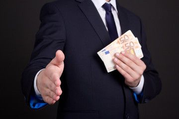 bribery concept - man in suit with money ready to handshake