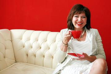 elegante Frau auf weißem Sofa trinkt Kaffee