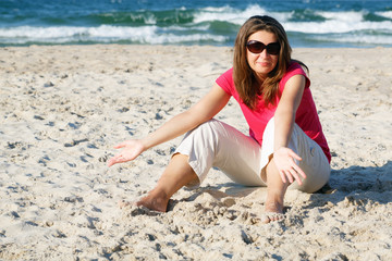 Gesticulating woman on the beach in sunglasses