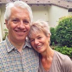 Paar Senioren lächelt vor Haus