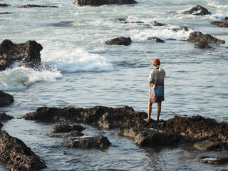 A man fishing on rocks