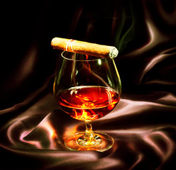 Cognac and cigar. Glass of brandy over dark background