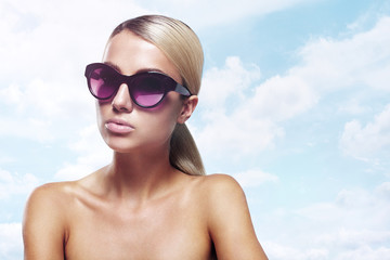 Blondie in sunglasses on the beach