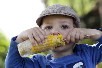 Hungry kid eating corn