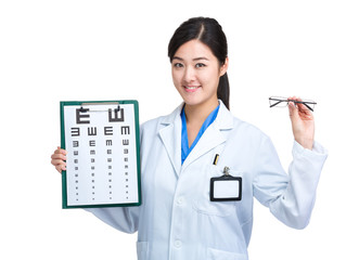 Female optician doctor hold glasses and showing eye chart