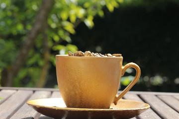 goldfarbene Kaffeetasse auf Holztisch