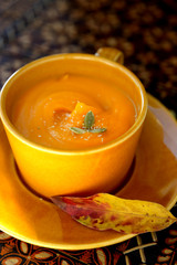 Pumpkin soup in a yellow bowl.