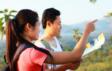Couple hikers holding map looking and pointing