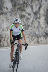 woman road cycling standing uphill