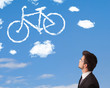 canvas print picture - Young man looking at bicycle clouds on blue sky