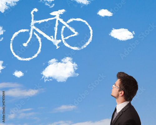 canvas print picture Young man looking at bicycle clouds on blue sky