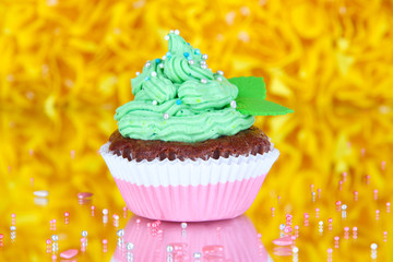 Delicious beautiful cupcake on decorative yellow background