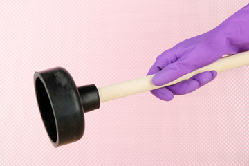 Toilet plunger in hand on pink background