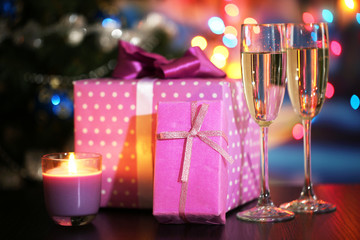 Many gifts and glass of champagne on bright background