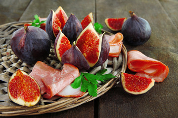 Tasty figs with ham on grey wooden table