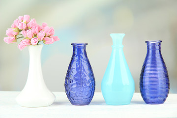 Different decorative vases on shelf on light background