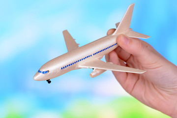 Toy airplane in hand on light blue background