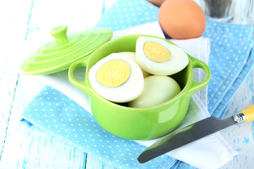 Boiled eggs in pan and eggcup on color wooden background