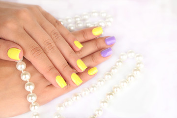 Female hand with stylish colorful nails and beads,