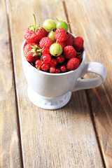 Forest berries in cup, on wooden table background