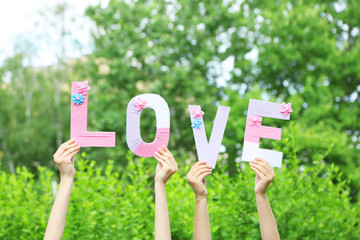 Hands holding up letters building word love