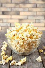 Popcorn in bowl on wooden table, close up