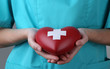 Red heart with cross sign in doctor hand, close-up,
