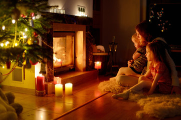Happy family by a fireplace on Christmas