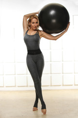 Beautiful woman blond hair standing holding up ball for fitness
