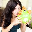 Woman kissing piggy bank happy