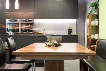 dining table with leather chairs and dark grey modern kitchen