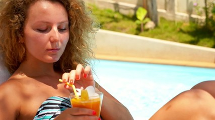 Close up of Woman Drinking Mango Juice near Swimming Pool.