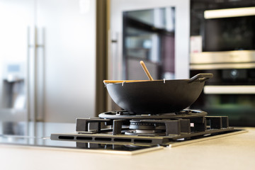 noodle wok on gas stove on workplate in modern kitchen