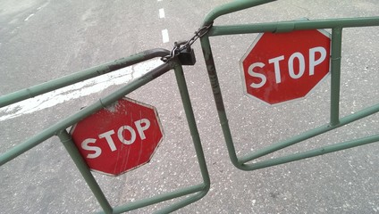 Stop road signs on locked metal gate