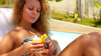 Beautiful Girl Drinking Fresh Mango Juice near Luxury Pool.