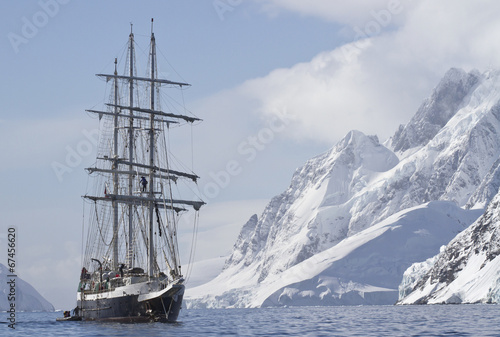 In de dag Antarctica tourist ship sailing summer day on a background of mountain peak