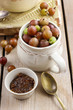 Jug of gooseberry fruits and bowl of gooseberry jam