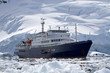 big blue tourist ship in Antarctic waters against the backdrop o - 67457295