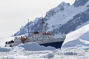 tourist ship among the icebergs on the background of the mountai