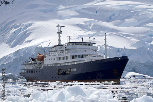 Staande foto Antarctica big blue tourist ship in Antarctic waters against the backdrop o
