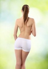 Body of woman ass and back on green background