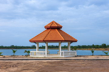 Pavilion on ground with lake and blue sky background