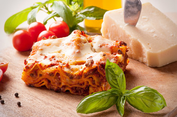 Lasagne with meat tomatoes and cheese sauce on a wooden board